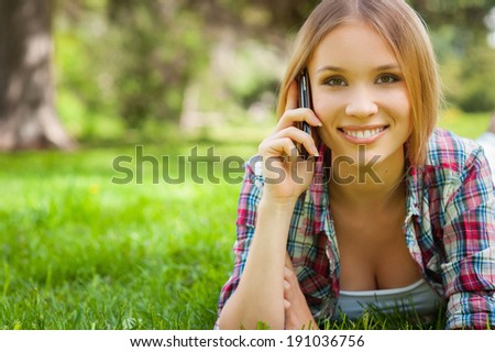 Always in touch. Beautiful young woman talking on the mobile phone and smiling while lying on the grass in park - stock photo
