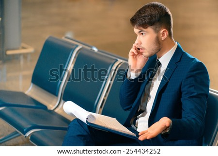 Always on the phone. Side view of handsome smiling businessman in formalwear holding a clipboard and talking over the mobile phone while sitting in the airport  - stock photo