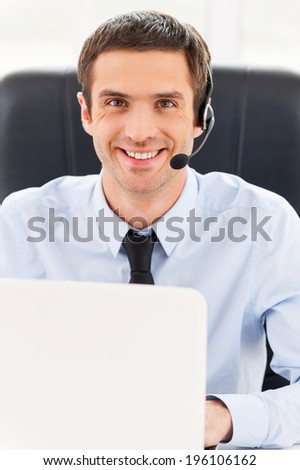 Always ready to help you. Cheerful young man in headset looking at camera while using laptop - stock photo