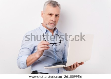 Always ready to help you. Confident senior man in shirt and eyeglasses holding laptop and looking at camera while standing against grey background - stock photo