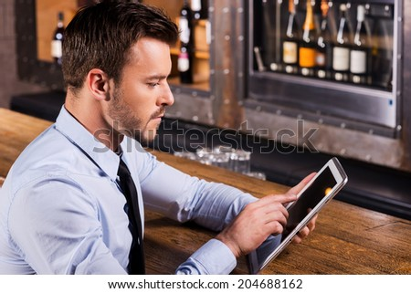 Always staying in touch. Confident young man in shirt and tie sitting at the bar counter and working on digital tablet - stock photo