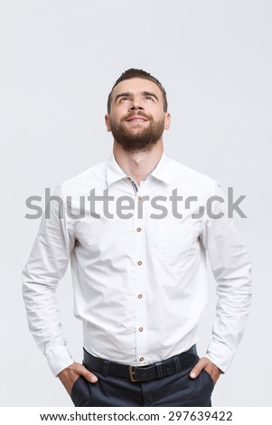 Always up. Middle-aged handsome smiling man with beard looking up and holding hands in pockets against isolated white background.