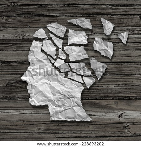 Alzheimer patient medical mental health care concept as a sheet of torn crumpled white paper shaped as a side profile of a human face on wood as a symbol for neurology and dementia or memory loss. - stock photo