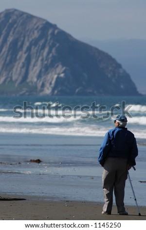 Am elderly person strolls down the beach alone. - stock photo