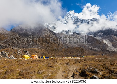 Ama Dablam mountain  base camp mountaineers alpinists expedition tents, mountain snow peak glacier. Everest Base Camp trekking route trail. Nepal tourism. - stock photo