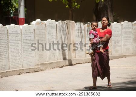 AMARAPURA, MYANMAR - JUNE 30 : Burmese mother and son through the ranks of the stone slabs of the Buddhist canon ( Tripitaka texts ) at the Maha Gandayon Monastery  on June 30,2014,Mandalay, Myanmar. - stock photo