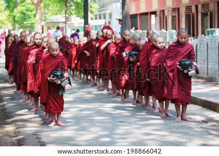 AMARAPURA, MYANMAR - MAY 01, 2012: young buddhist novices walk to collect alms and offerings in the monastery of Maha Gandhayon Kyaung near Mandalay in Myanmar. - stock photo