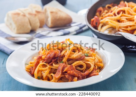 amariciana style fetuccini with bacon and tomato sauce on white bowl - stock photo