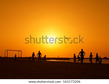 Amateurs playing football at Jumeira beach in Dubai during sunset. - stock photo