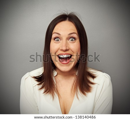 amazed and happy woman looking at camera over dark background - stock photo