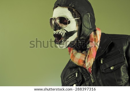 Amazed aviator with face painted as human skull - stock photo