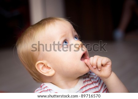 Amazed baby boy sucking his thumb - stock photo