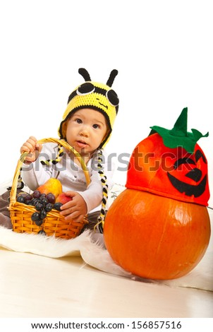 Amazed baby in bee hat holding basket with grapes and pears and sitting on fur blanket near pumpkin with halloween hat - stock photo
