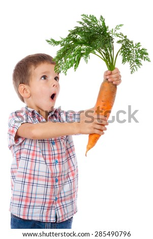 Amazed boy stands with big sized carrot, isolated on white - stock photo