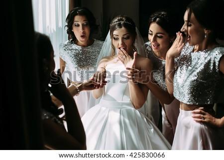 Amazed bride and her glamorous girls - stock photo