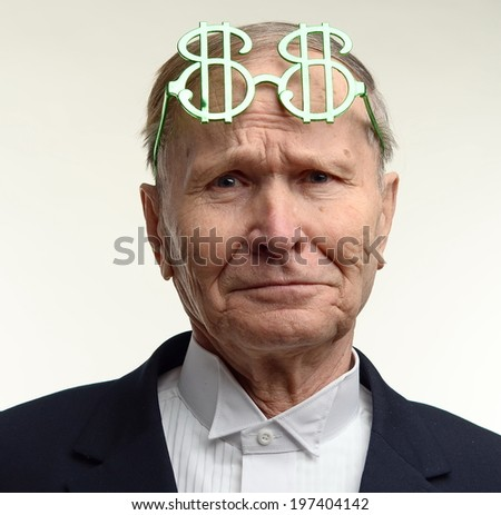 Amazed business man with dollar sign glasses on forehead - stock photo