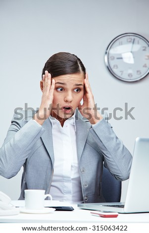 Amazed businesswoman sitting in front of laptop - stock photo