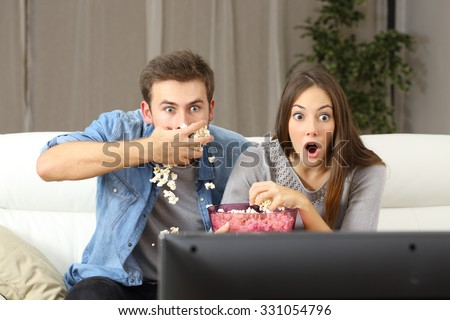 Amazed couple watching tv program sitting on a couch at home - stock photo