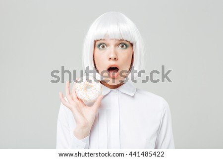 Amazed cute young woman in blonde wig holding donut - stock photo