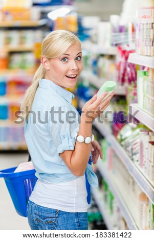 Amazed girl at the shop choosing cosmetics among the great variety of products. Concept of consumerism, retail and purchase - stock photo
