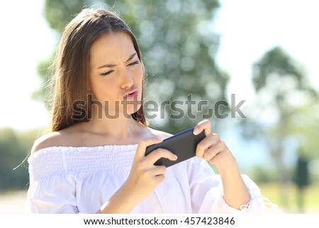 Amazed girl playing games on line with a smart phone in a park