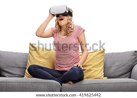 Amazed girl sitting on a gray sofa and looking in VR goggles isolated on white background - stock photo