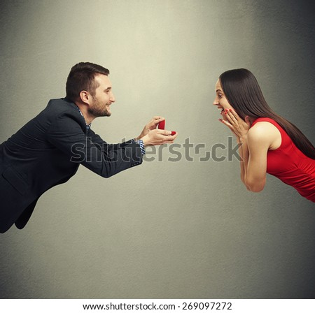 amazed happy woman looking at the ring that holding the man. photo on dark background - stock photo