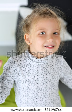 Amazed little blonde girl looking in camera portrait. Smiling female child with funny face standing and posing. Kid playing games using imagination. Family concept