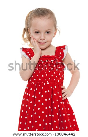Amazed little girl in a red dress on the white background