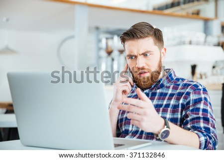 Amazed man talking on the phone and looking on laptop compter in coffee shop - stock photo