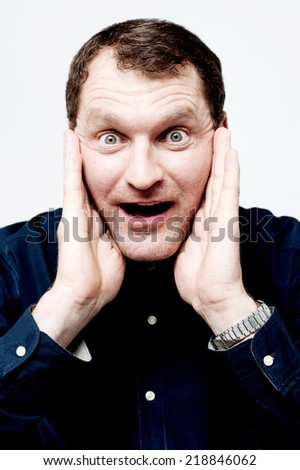 Amazed middle aged man covering his ears - stock photo