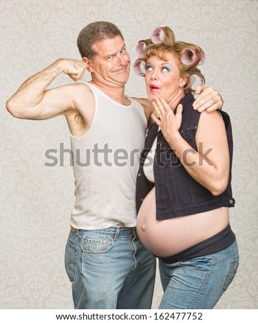 Amazed pregnant hillbilly woman and man flexing biceps - stock photo