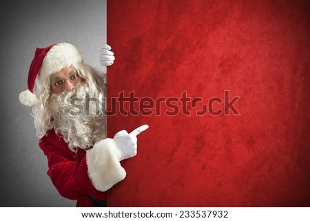 Amazed santa claus indicates a red billboard - stock photo