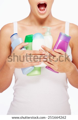 Amazed woman holding containers with bodycare products