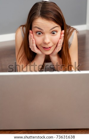 amazed woman looking on laptop and lying on floor - stock photo