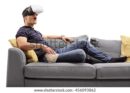 Amazed young man looking in VR goggles and eating popcorn seated on a sofa isolated on white background - stock photo