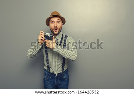 amazed young man with camera over grey background - stock photo
