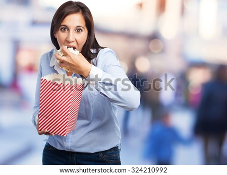amazed young woman eating popcorn - stock photo