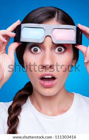 amazed young woman in 3d glasses over blue background