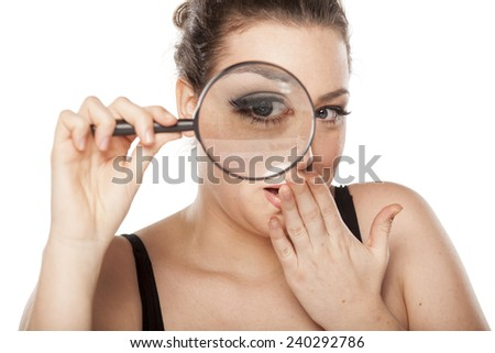 amazed young woman looking through a magnifying glass