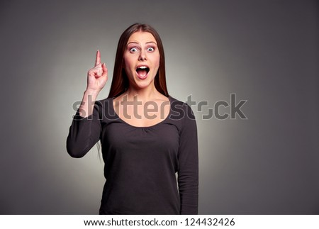 amazed young woman pointing upward over dark background - stock photo