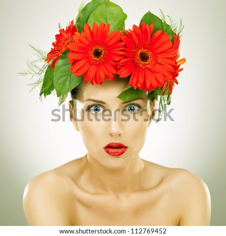 amazed young woman with red gerbera flowers on her head looking at the camera - vintage picture style
