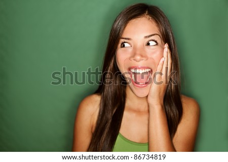 amazement - woman excited looking to the side. Surprised happy young woman looking sideways in excitement. Mixed race Chinese Asian / white Caucasian female model on green background. - stock photo