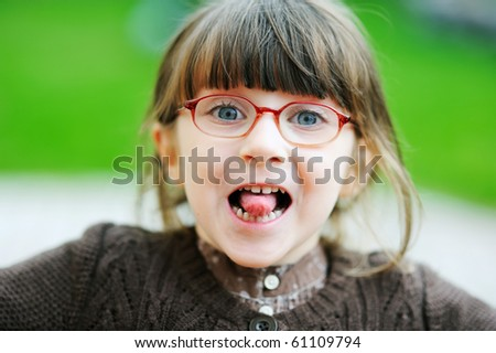 Amazing adorable little girl in glasses shows her tongue - stock photo