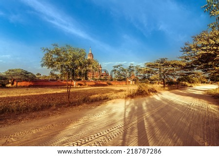 Amazing architecture of old Buddhist Temples at Bagan Kingdom. Empty road going through rural landscape under sunset sky near Sulamani pagoda. Myanmar (Burma) travel landscapes and destinations - stock photo