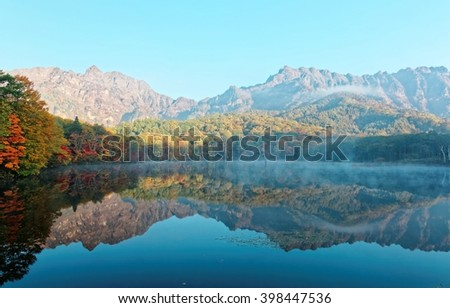 Amazing autumn lake scenery of Kagami Ike (Mirror Pond) in morning light with symmetric reflection of colorful fall foliage on smooth water & rugged Togakushi Mountain in background in Nagano Japan - stock photo