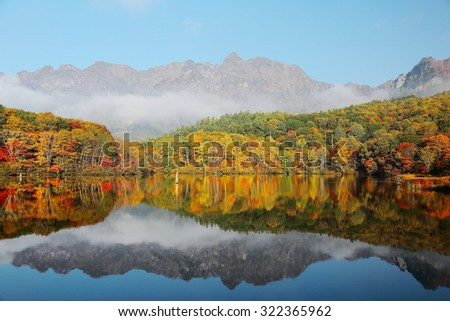 Amazing autumn lake scenery of Kagami Ike (Mirror Pond) with symmetric reflection of colorful fall foliage on smooth water & Mountain Togakushi in the background ~ Beautiful landscape of Nagano, Japan - stock photo