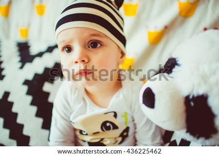 amazing baby sits on a sofa with plush panda - stock photo