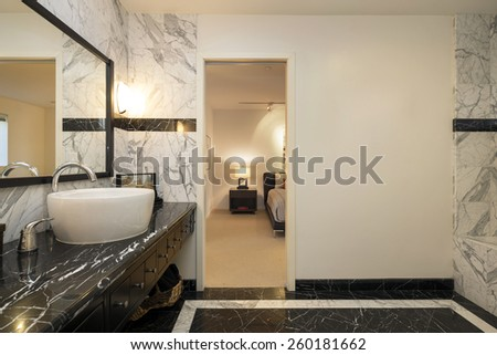 Amazing bathroom with single White round Sink on black marble counter with rectangle framed mirror. - stock photo