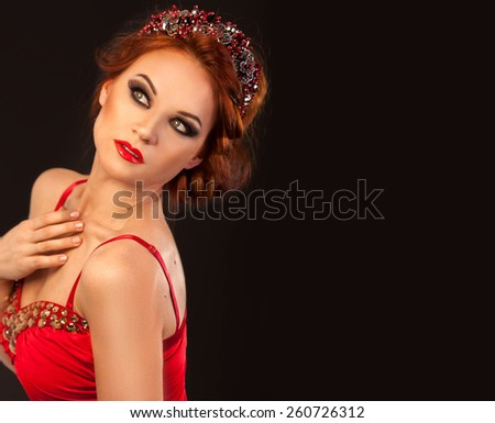 Amazing beautiful red hair woman with party make up in red dress with golden crystals and luxury princess tiara dreaming posing tender on black background with copyspace - stock photo